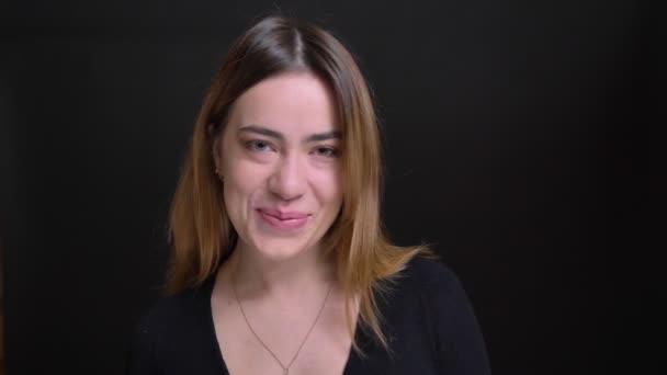 Detailní portrét mladých ohromující kavkazské ženy usmívá a směje se s plachost při pohledu na fotoaparát