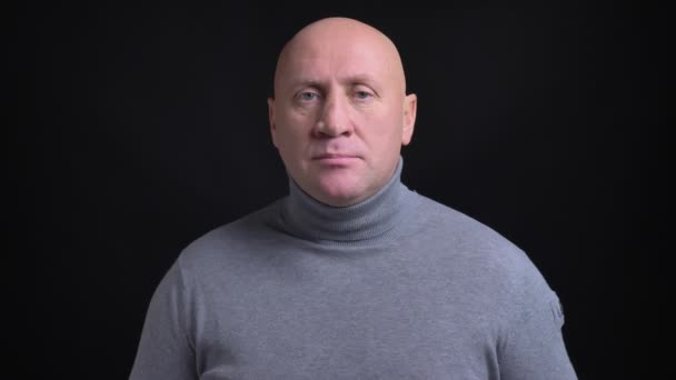 Closeup portrait of adult bald caucasian man in gray turtleneck looking straight at camera with background isolated on black