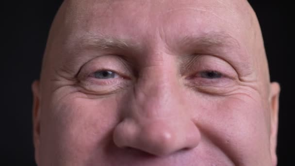 Closeup portrait of middle-aged caucasian man with eyes looking straight at camera with smiling facial expression.