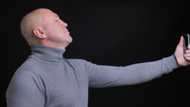 Closeup portrait of adult caucasian man taking selfies on the phone with background isolated on black