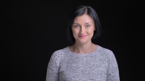 Closeup Portrait der jungen schönen kaukasischen Frau mit kurzen schwarzen Haaren lecken ihre Lippen und verführerisch beim Blick geradeaus in die Kamera Lächeln