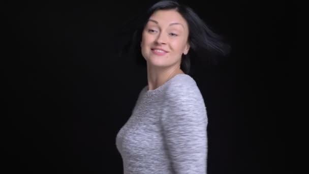 Vértes portré fiatal gyönyörű kaukázusi nő fordult a kamera mosolyogva, és így egy szem wink