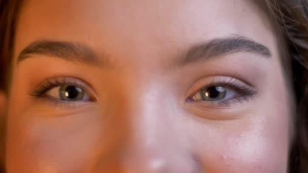 Detail očí portrét mladé kavkazský dívky s úsměvem dívat do kamery na rozostřené pozadí světla.