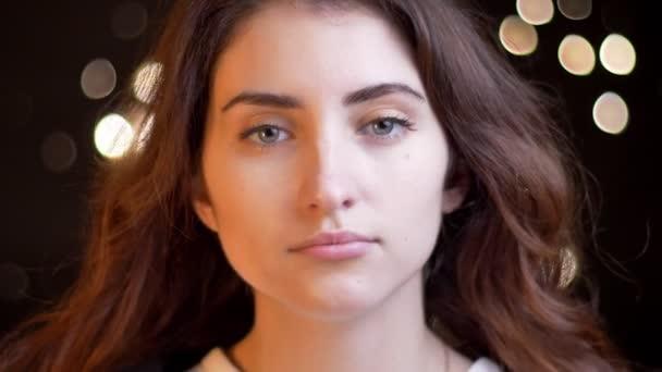 Nahaufnahme Porträt eines jungen kaukasischen Mädchens, das ernsthaft in die Kamera schaut und auf verschwommenem Licht die Haare schüttelt.