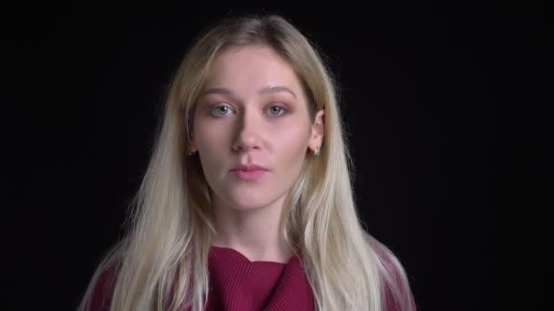 Closeup hajtás fiatal csinos kaukázusi szőke nő keres egyenesen a kamera semleges arckifejezés