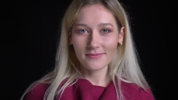 Closeup hajtás fiatal vonzó kaukázusi nő szőke haja csábítóan mosolyogva és keres egyenesen a kamera
