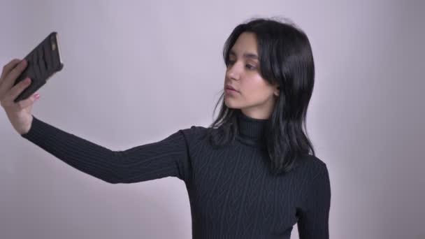 Vértes lő a fiatal szép kaukázusi nő figyelembe selfies a telefon, a kamera előtt
