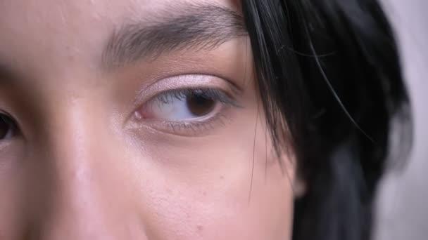 Vértes fél arcát portré fiatal vonzó kaukázusi Fekete hajú női arc gyönyörű szemmel nézett egyenesen a kamera