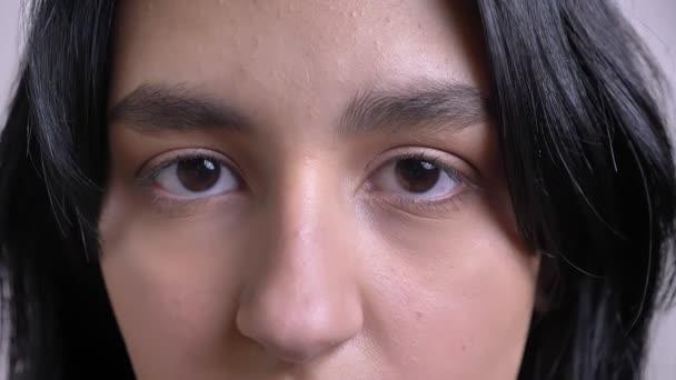 Vértes lő fiatal vonzó kaukázusi Fekete hajú női arc, gyönyörű szemekkel nézett egyenesen a kamera