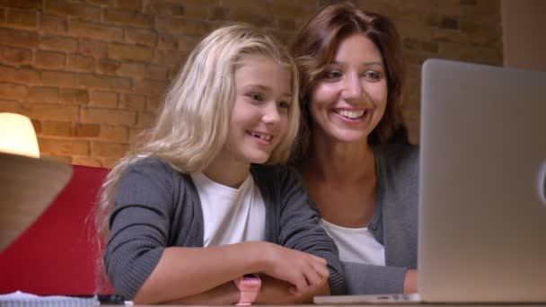 Closeup portrait of young mother and her daughter watching a movie on the laptop smiling and laughing at home indoors