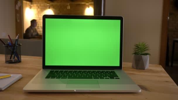 Nahaufnahme eines grünen Bildschirms des Laptops, der im Büro auf dem Schreibtisch liegt und im Hintergrund arbeitet