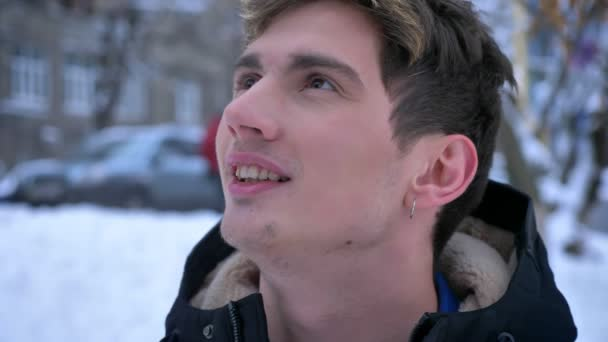 Closeup shoot of young attractive caucasian dreaming and smiling while looking at camera outdoors in a snowy winter day