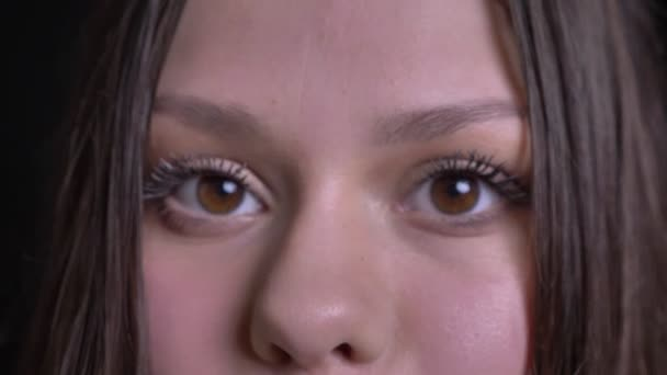Closeup střílet mladých atraktivních kavkazské ženské tváře s hnědýma očima s nádherné líčení, díval se přímo na kameru