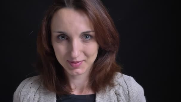 Portrait of middle-aged brunette caucasian woman smiling shyly into camera on black background.