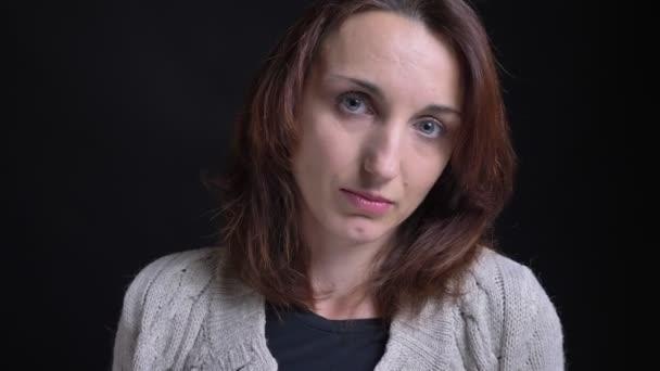 Középkorú barna kaukázusi nő negatívan fordult meg a fejét a fekete háttér kamera közelről portréja.