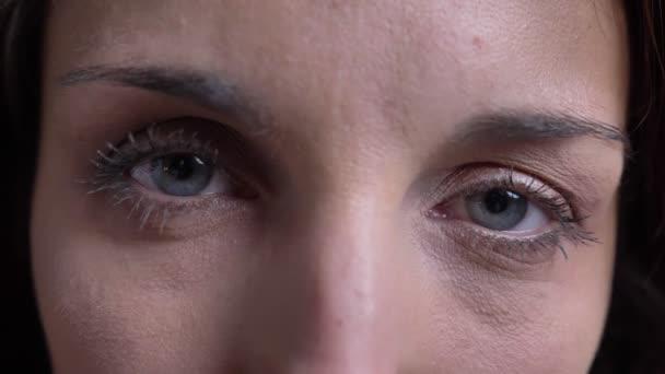 Detail očí portrét bruneta kavkazské ženy středního věku pozorně dívat do kamery na černém pozadí.