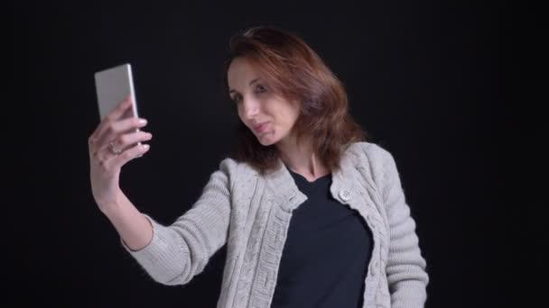 Porträt einer brünetten kaukasischen Frau mittleren Alters, die Selfie-Fotos mit dem Smartphone auf schwarzem Hintergrund macht.