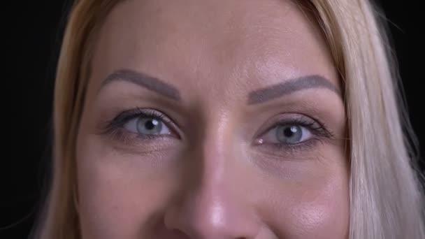 Vértes lő a közepén éves kaukázusi női arc, szürke szemmel nézett egyenesen a kamera a mosolygó arc kifejezése