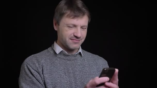 Nahaufnahme von erwachsenen attraktiven kaukasischen Männern, die am Telefon SMS schreiben und vor der Kamera lächeln