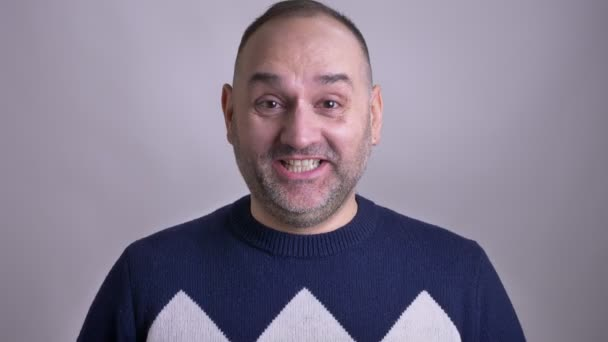 Closeup shoot of middle aged caucasian man smiling happily while looking at the camera
