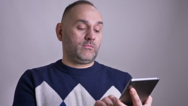 Closeup shoot of middle aged caucasian male browsing on the laptop and showing green chroma screen to camera smiling