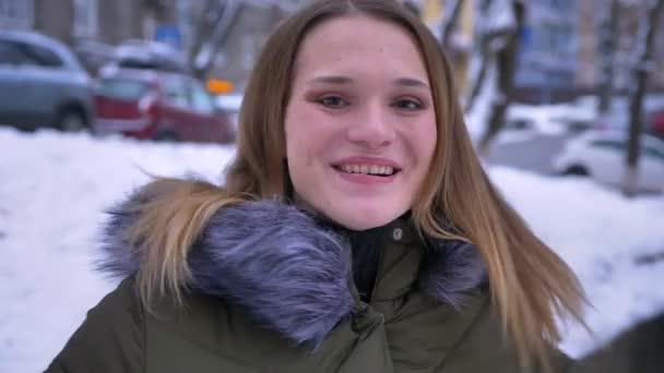 Closeup natáčení mladé krásné kavkazské bruneta žena být šťastný a výskok z radosti, smíchu a otočil v zasněžený den při pohledu na fotoaparát