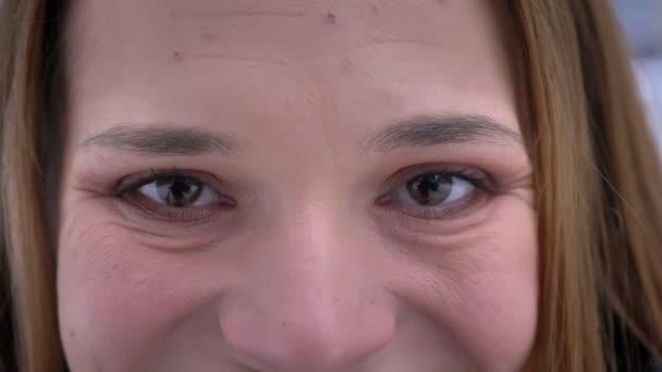 Vértes portré fiatal szép kaukázusi női arc, barna szemekkel nézett egyenesen a kamera a mosolygó arc kifejezése