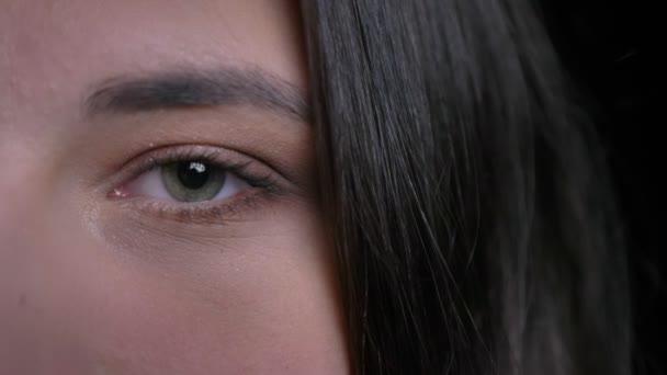 Vértes fél arcát portré fiatal vonzó kaukázusi nő-zöld szemmel nézett egyenesen a kamera