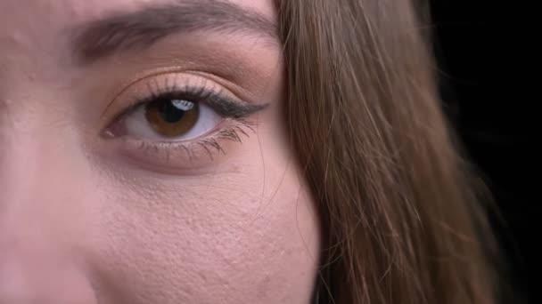 Closeup poloobličejových portrét mladé krásné kavkazské ženské tváře s její oči hledí přímo na kameru s pozadím, samostatný na černém pozadí