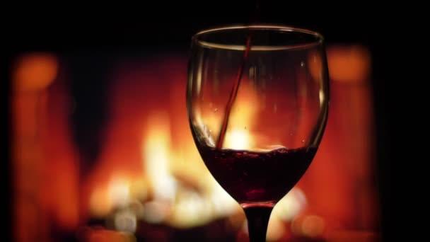 Nahaufnahme Shooting von Rotwein in das leere Glas mit gemütlich warmen Kamin mit Flammen auf dem Hintergrund drinnen in einer dunklen Wohnung gegossen