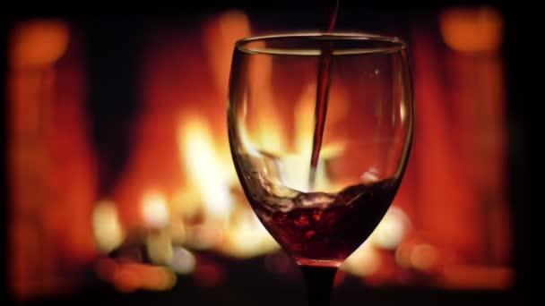 Nahaufnahme Shooting von Rotwein in das luxuriöse leere Glas mit gemütlich warmen Kamin auf dem Hintergrund drinnen in einer dunklen Wohnung gegossen