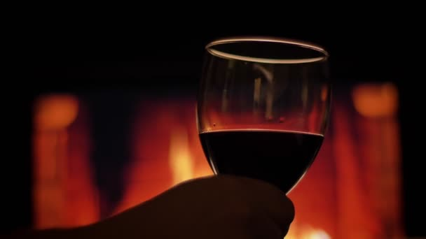 Nahaufnahme Rückseite Shooting der Hände hält ein Glas mit Rotwein mit gemütlich warmen Kamin mit Flammen auf dem Hintergrund drinnen in einer dunklen Wohnung
