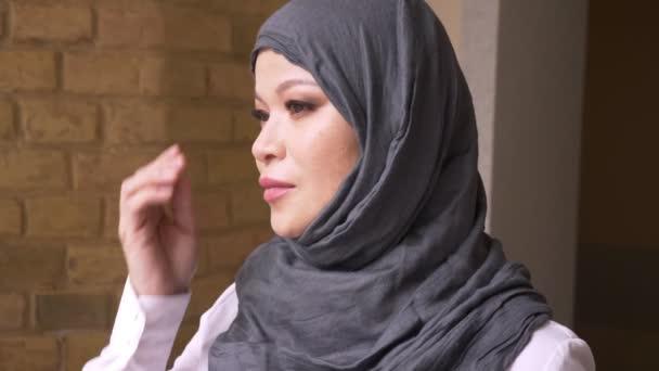 Nahaufnahme einer erwachsenen muslimischen Geschäftsfrau im Hidschab, die sich am Arbeitsplatz nach drinnen freut