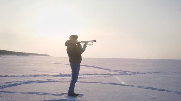 Dolly zoom in shot of alone caucasian musician in profile playing trumpet actively in sunshine on frozen nature background.