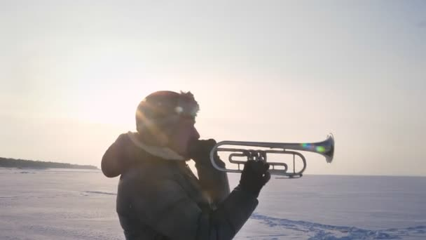 Dolly zooming out shot of delighted caucasian musician in profile playing trumpet in sunshine on frozen nature background.