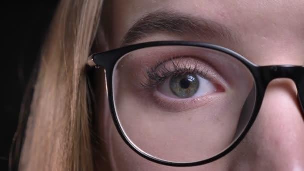 Closeup poloobličejových natáčení mladé atraktivní bokovky ženské tváře v brýlích a s očima díval přímo na kameru