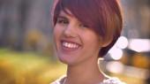Hűvös kaukázusi rózsaszín hajú kislány boldogan néz a napos park háttér kamera közelről portréja.