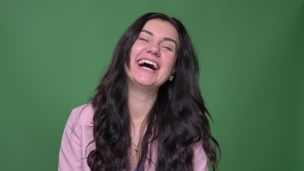 Portrait of brunette businesswoman in pink jacket laughing joyfully into camera on green background.