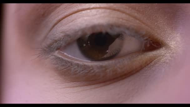 Closeups poloobličejových střílet ženské tváře s hnědé oko hledí přímo na kameru s make-up nanáší