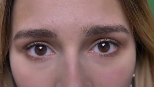 Closeup lő fiatal vonzó csípő kaukázusi női arc szemmel, hogy zárva, akkor nézett egyenesen a kamera háttérrel izolált zöld