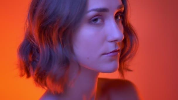 Nahaufnahme Seitenansicht Shooting der jungen attraktiven kaukasischen Frau mit Nasenpiercing Blick in die Kamera mit neonrotem Hintergrund