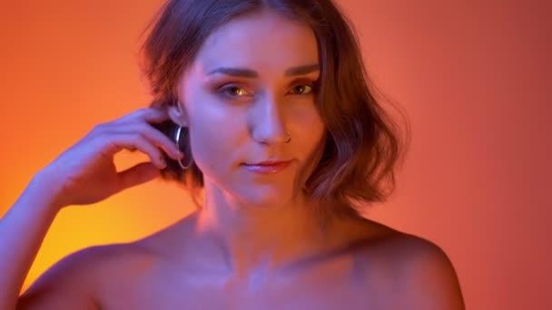 Primo piano sparare di giovane femmina caucasica seducente con le spalle nude giocando con i suoi capelli guardando fotocamera con sfondo rosso neon