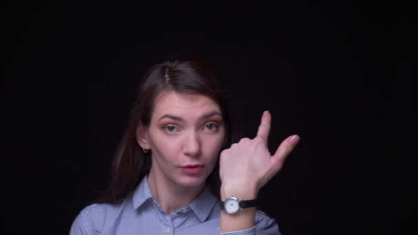Portrait of young brunette businesswoman in blue blouse dancing weirdly into camera at black background.