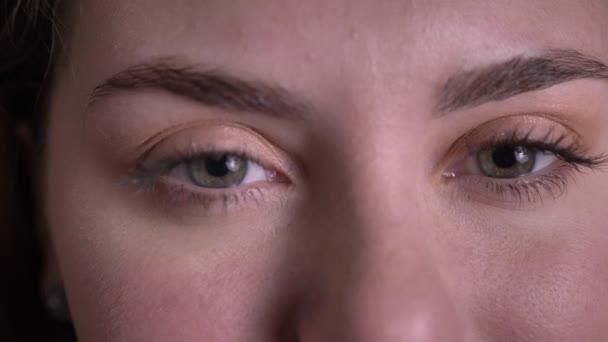 Blízký portrét krásné blonďaté ženy otevírá oči a s úsměvem pozoruje kameru na černém pozadí.