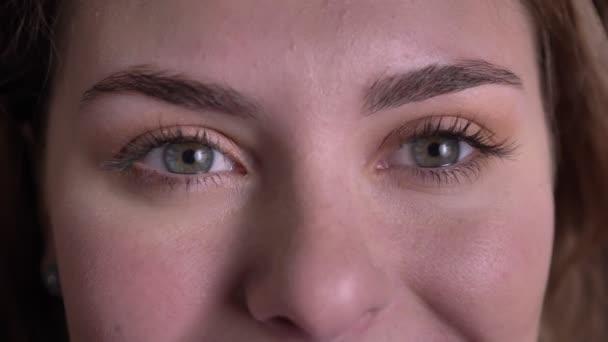 Közelről Eye-portré gyönyörű szőke nő nézi mosolygóan bal és a kamera fekete háttér.