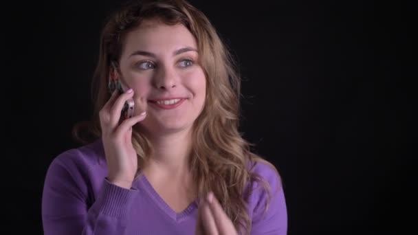 Portré boldog szőke nő, amelynek hanghívás a smartphone fekete háttér.