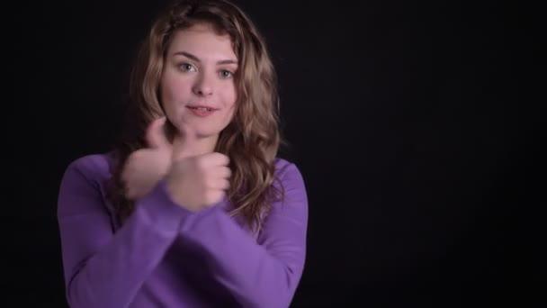 Portrét roztomilej ženský gestikulovat nápisy do kamery, aby ukázala jako respekt na černém pozadí.
