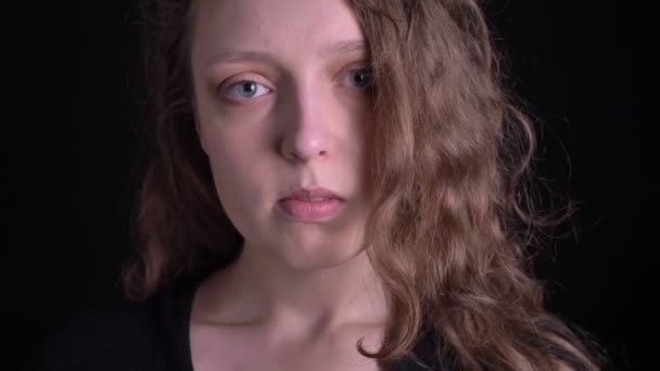 Portrait of young curly-haired girl watching intently and seriously into camera on black background.