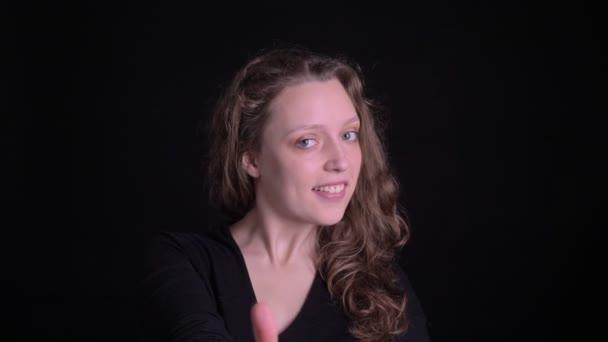 Portré fiatal göndör hajú lány, gesztő ujj-up mutatja, mint a és a tisztelet a kamera fekete háttér.