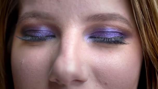 Closeup lő fiatal csinos női arc szemmel nézte a kamerát mosolygós boldogan lenyűgöző smink háttérrel izolált fekete